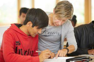 Melita Scheibeck zeigt einem Schüler etwas in einem Buch